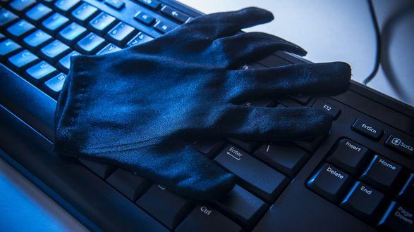 Обои Черная перчатка лежит на компьютерной клавиатуре