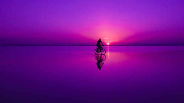 Обои Мужчина едет на велосипеде по мелководью, при фиолетовом освещении заходящего солнца