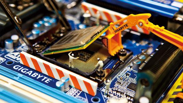 Обои Маленькие игрушечные человечки, с помощью игрушечного трактора, поднимают процессор из разъема сокет в материнской плате марки Gigabyte, на процессоре надпись king of diy / король сделай сам