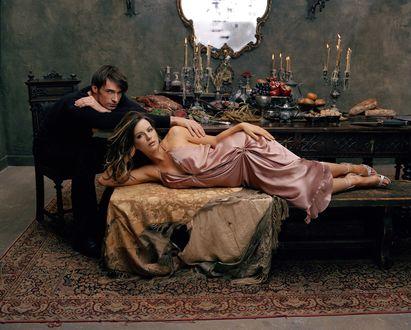 Обои Актер Хью Джекман / Hugh Jackman и актриса Кейт Бекинсейл / Kate Beckinsale, за накрытым столом, актриса лежит на скамейке с оборванным покрывалом, актер сидит на стуле позади, положив свою руку на плечо девушки