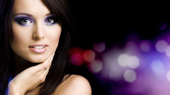Обои На фоне разноцветных бликов девушка с красивым макияжем приложила руку к своей шее
