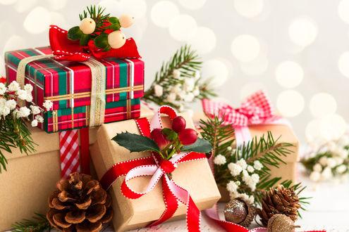 Обои Красиво упакованные новогодние подарки, сосновые веточки и шишки на светлом фоне