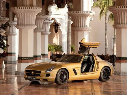 Обои Золотистый автомобиль марки Mercedes AMG стоит на фоне колонн дома
