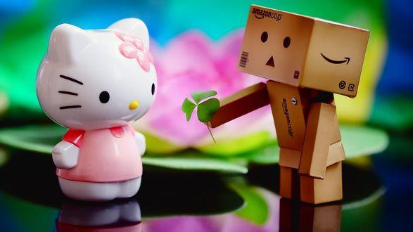 Обои Картонный человечек дарит листочек клевера игрушке Hello Kitty / Привет Кошечка, на размытом фоне