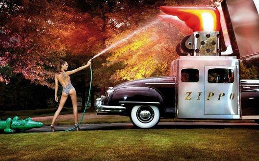 Обои Девушка модель направляя воду из шланга на горящую машину не может погасить огонь - реклама зажигалок ZIPPO
