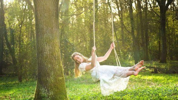 Обои Девушка катается на качелях на лесной полянке