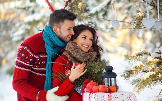 Обои Влюбленная пара в зимнем лесу, в руках у девушки цветы, рядом стоит столик, на нем лежит фонарь и гранаты, на ветке ели, висят сердечки