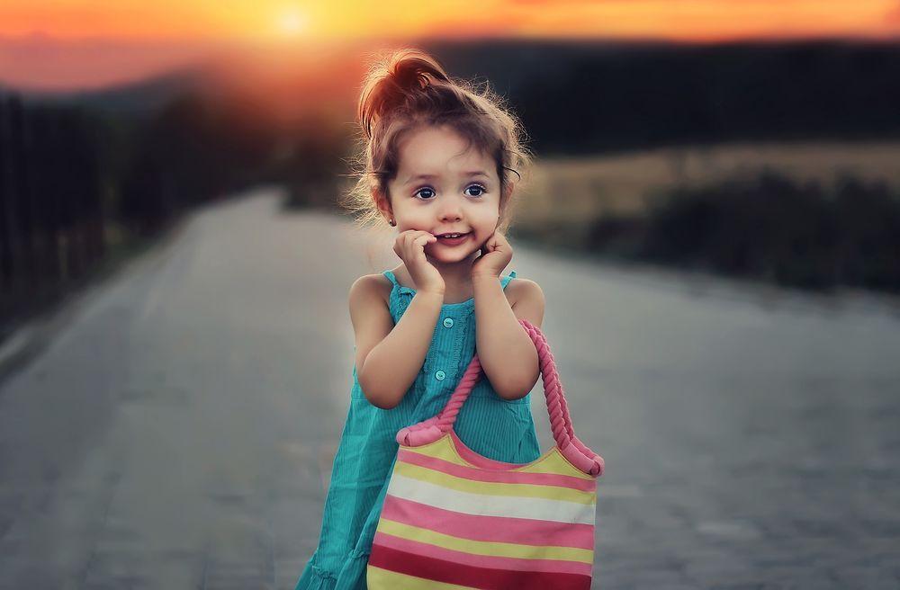 Обои для рабочего стола Маленькая, радостная девочка с полосатой сумкой, стоит на дороге на размытом фоне
