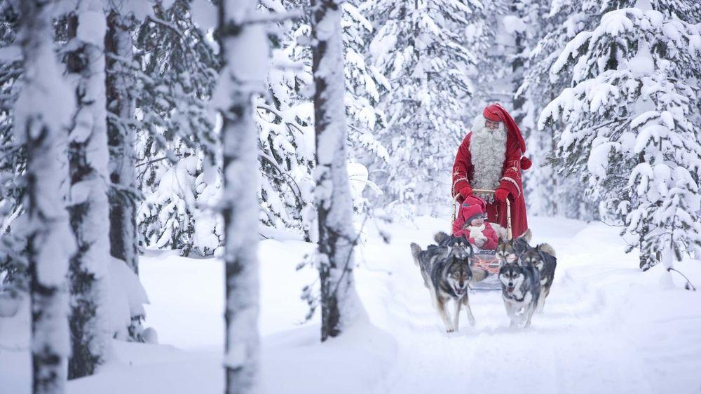 Обои для рабочего стола Дед Мороз на упряжке с собаками спешит к детям