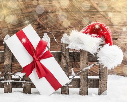 Обои Коробка с подарком и новогодний колпак на деревянном заборе