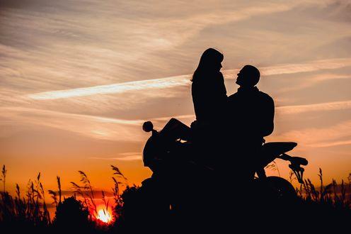 Обои Парень с девушкой сидят на мотоцикле на закате