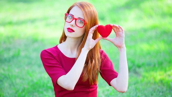 Обои Рыжая девушка в красных очках и платье держит сердечко в руках