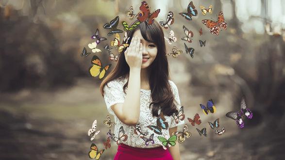 Обои Девушка с улыбкой прикрыла лицо рукой, вокруг порхают бабочки