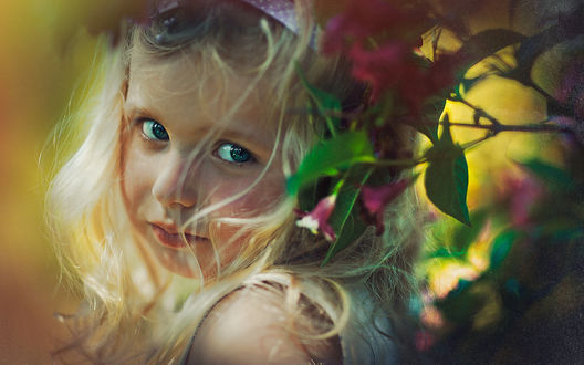 Обои На фоне цветущего куста девочка с длинными въющимися волосами, обернувшись назад пристально смотрит