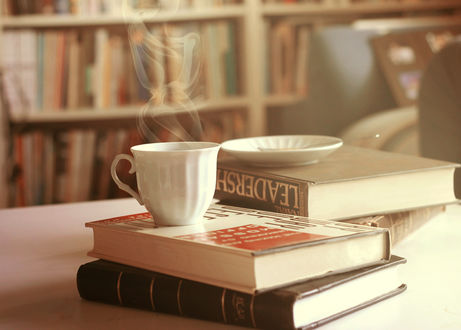 Обои Кружка с горячем чаем стоит на книгах на столе в библиотеке