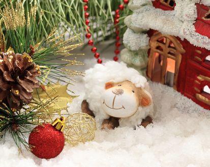 Обои Игрушечная овечка в искусственном снегу рядом с елочными игрушками