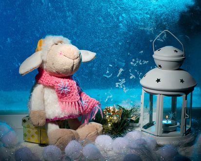 Обои Игрушечная овечка сидит на коробке с подарком, рядом фонарь с горящей свечой