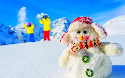 Обои Яркий Снеговик в снегу в горах на фоне лыжников