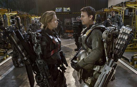 Обои Том Круз и Эмили Блант в роли Билла Кейджа и Риты Вратаски из фильма Грань будущего стоят друг напротив друга одетые в боевые экзоскелеты