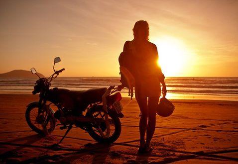 Обои Девушка стоит рядом с мотоциклом на берегу моря и смотрит на закат