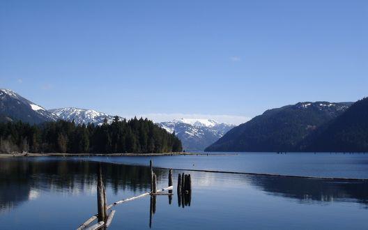 Обои В озере стоят деревянные остовы разрушенного моста, вдоль берега растут деревья, на заднем плане видны горы, покрытые снегом