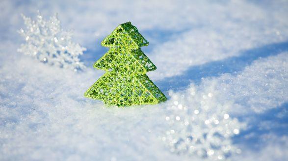 Обои Фигурка елочки и снежинки на снегу