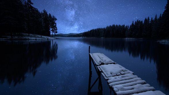 Обои Заснеженный мостик у лесного озера, в котором отражается звездное небо