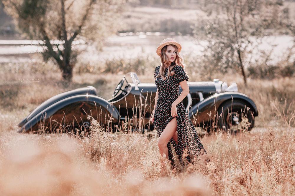 Обои для рабочего стола Девушка стоит в траве, за ней -авто, ву Irina Dzhul