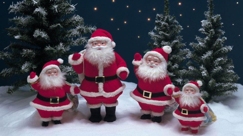 Обои для рабочего стола Деды Морозы стоят на полянке и машут рукками
