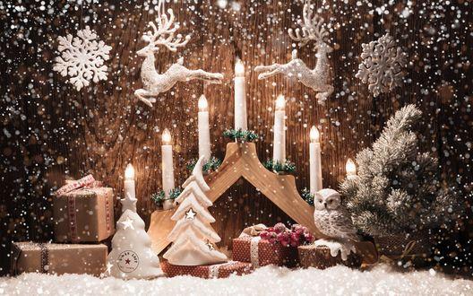 Обои Фигурки оленей висят над зажженными свечами и подарками, на пеньке стоит фигурка совы