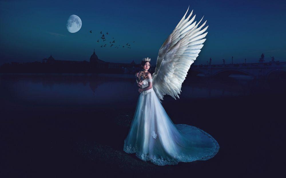 Обои для рабочего стола Девушка-ангел с букетом цветов стоит у воды