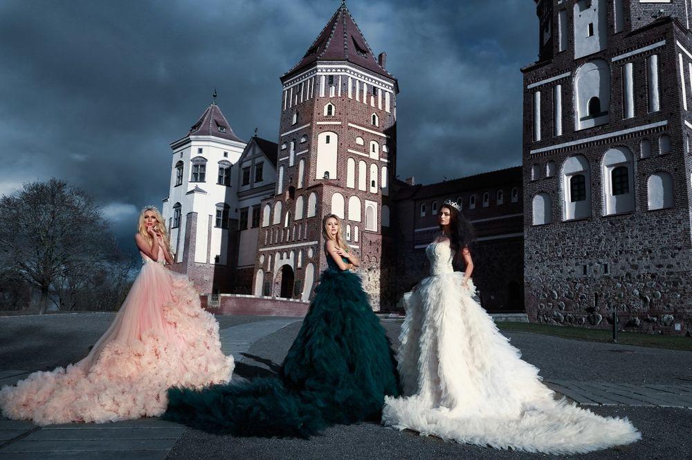 Обои для рабочего стола Три девушки в длинных платьях стоят на фоне замка