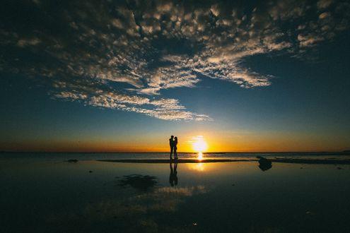 Обои Парень и девушка стоят обнявшись на песчаной полосе в море на фоне заходящего солнца и неба с перистыми облаками, автор Dani Virov