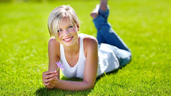 Обои Голубоглазая блондинка с цветком в руке лежит на зеленой траве и нежно улыбается