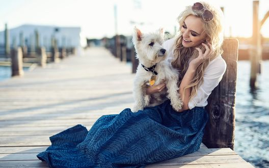 Обои Блондинка сидит с собакой на причале и улыбается