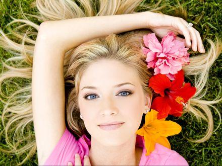 Обои Голубоглазая блондинка с цветами в волосах лежит на траве