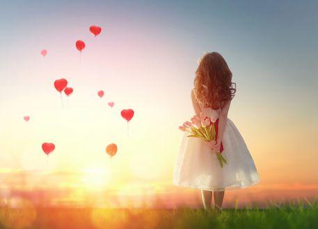 Обои Девочка в белом платье держит за спиной букет цветов на фоне заката солнца и шаров в небе в форме сердечка