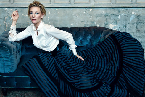 Обои Актриса Cate Blanchett в белой блузке и полосатой юбке сидит на диване
