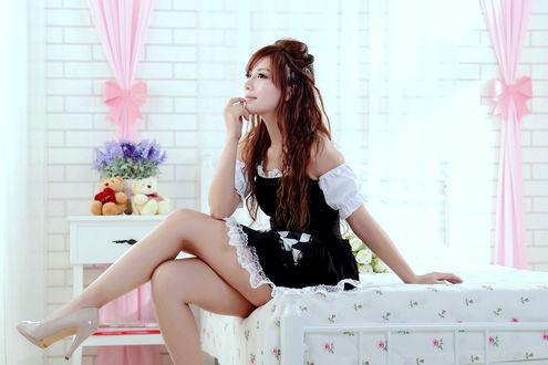 Обои Азиатка в костюме горничной сидит на кровати