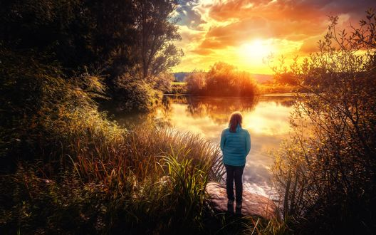 Обои Девушка стоит на камне у озера и смотрит на закат солнца