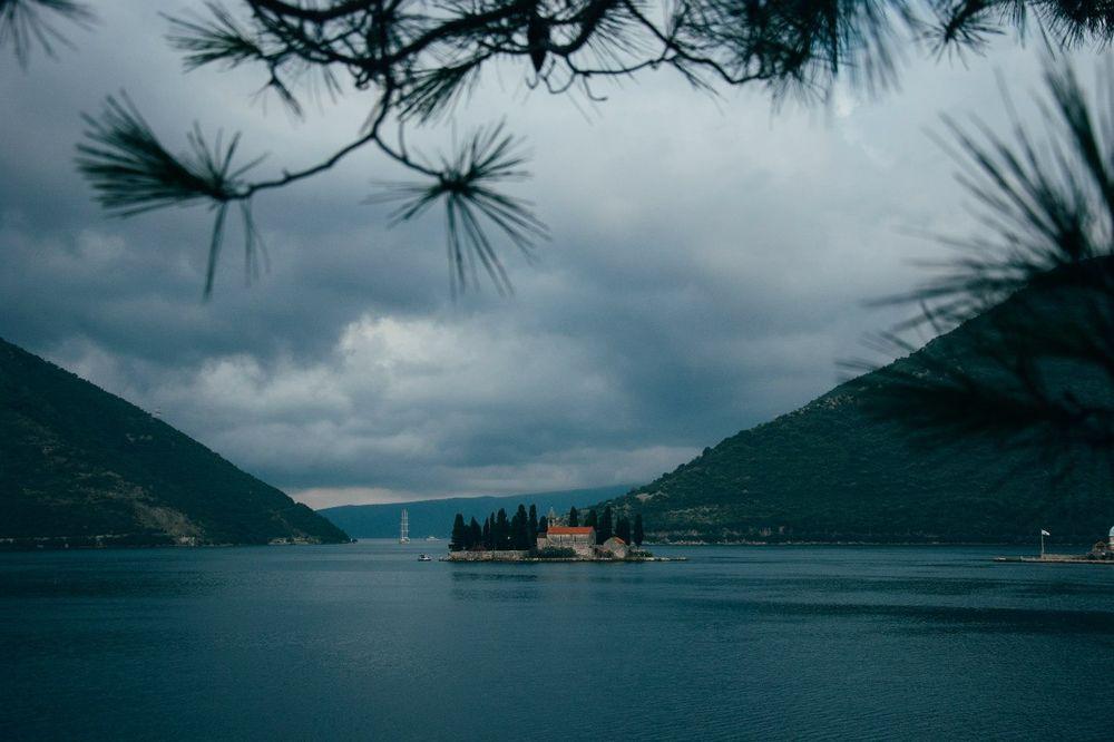 Обои для рабочего стола Между горами в центре озера находится остров с деревьями и домом, автор Ксения Сольвейг