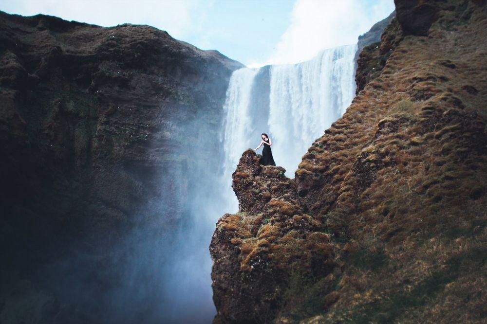 Обои для рабочего стола Девушка стоит на скале у водопада, by Alexey Demshin