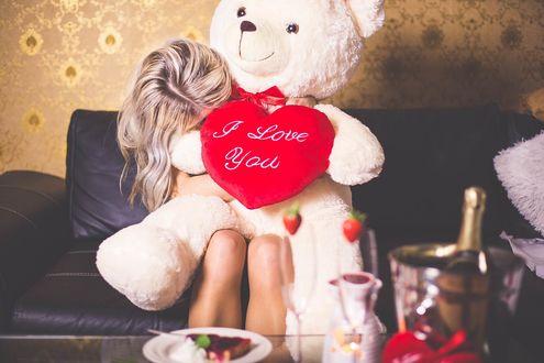 Обои Девушка в обнимку с плюшевым медведем, который держит сердечко с надписью I love you / Я тебя люблю сидит на диване