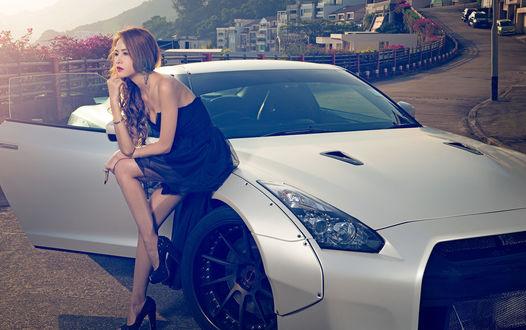 Обои Задумчивая девушка в черном платье, сидит на капоте машины, на фоне дороги