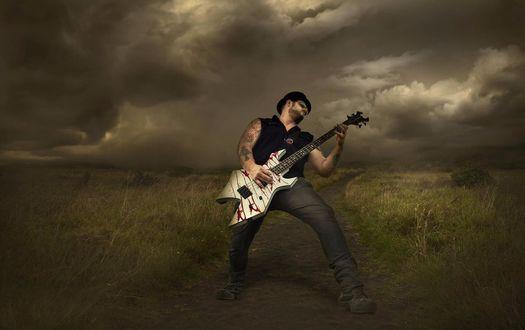 Обои Рок музыкант исполняет соло на электрогитаре, стоя на проселочной дороге