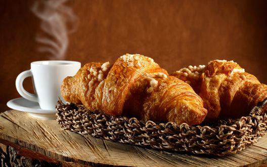 Обои Два круасана в плетенной тарелке и чашка кофе в белой посуде на деревянном столе
