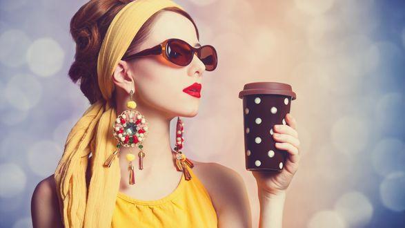 Обои Девушка в желтом с ярким макияжем, в очках, серьгах, держит коричневый стакан с кофе