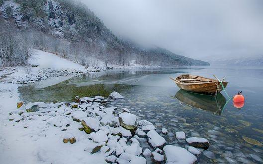 Обои Деревянная лодка недалеко от заснеженного берега