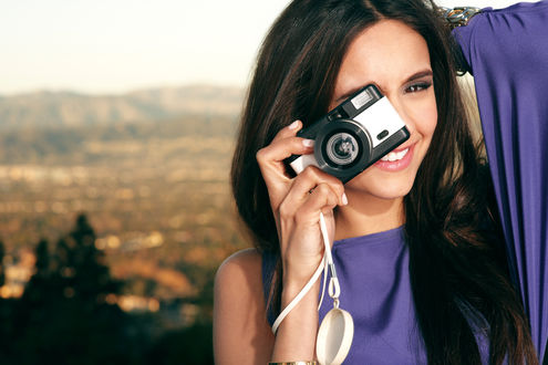 Обои Нина Добрев, актриса, в фиолетовом платье держит фотоапарат и нежно улыбается