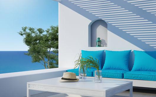 Обои Балкон дома у моря, голубой диван, шляпа на столе